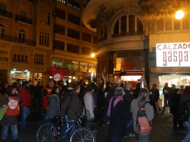 """[Crónica] CNT inicia el conflicto contra la Pizzería Ñam Ñam con una concentración frente a la misma  El Sindicato CNT se concentra frente a la Pizzería Ñam Ñam, situada en el centro histórico de Valencia, para protestar contra los despidos e impagos que han sufrido dos de sus trabajadoras.  El pasado viernes 17 de enero a las 19:30, una veintena de afiliados/as y simpatizantes del sindicato CNT-Valencia se concentraron frente a la Pizzería Ñam Ñam de la calle San Vicente, como muestra de solidaridad con dos de sus trabajadoras recientemente despedidas.  Como ya se indicó en una publicación anterior, el motivo del despido fue simplemente que las compañeras tuvieron la valentía y la dignidad de reclamar los derechos laborales que les estaban siendo negados en esta empresa que no duda en mantener a algunos de sus trabajadores sin contrato ni cotización a la Seguridad Social y con unos salarios que se encuentran muy por debajo de lo establecido en el Convenio de Hostelería. Además, amparándose en esta situación de clandestinidad en la que se encontraban sus trabajadoras, no sólo las ha dejado en la calle si no que no les ha pagado lo que les debe y ha hecho caso omiso a los numerosos intentos de CNT-Valencia de llegar a una solución favorable para las afiliadas, razón por la cual la asamblea del sindicato decidió iniciar el conflicto con la citada concentración informativa.  Dada la céntrica situación del local (entre la Plaza del Ayuntamiento y la de la Reina), numerosas personas se acercaron a informarse de las razones del conflicto, agotándose en apenas una hora el medio millar de octavillas que se repartieron en las inmediaciones de la pizzería. Además se cantaron consignas como """"Boicot a Ñam Ñam"""" o """"No compres aquí por solidaridad"""" que tuvieron una amplia acogida entre los transeúntes, lo cual se vio no sólo en las numerosas muestras de apoyo recibidas sino también en el hecho de que durante la hora y media que duró la concentración, la clientela del local brilló """